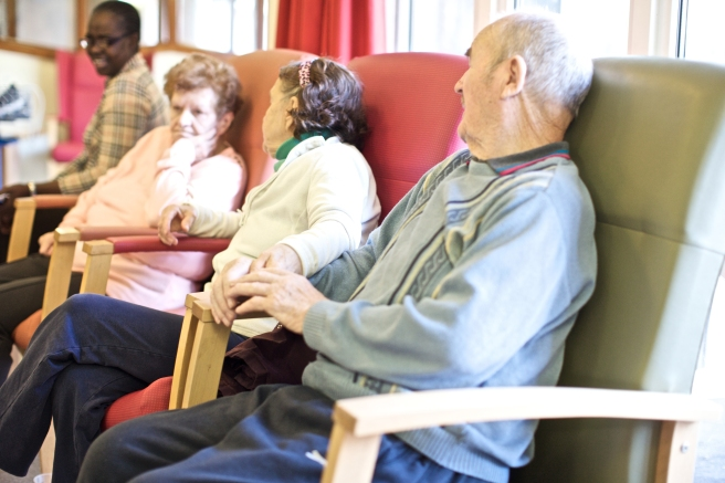 A psychiatric hospital, providing talking therapies, medication and social care support for people with mental health problems. The lounge or public space. Patients and staff. A day room. Three elderly people and a staff member.